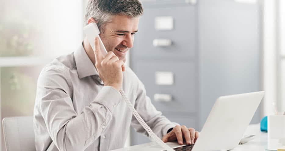 Photo of a smiling man on phone in front of a laptop in a small or home office.