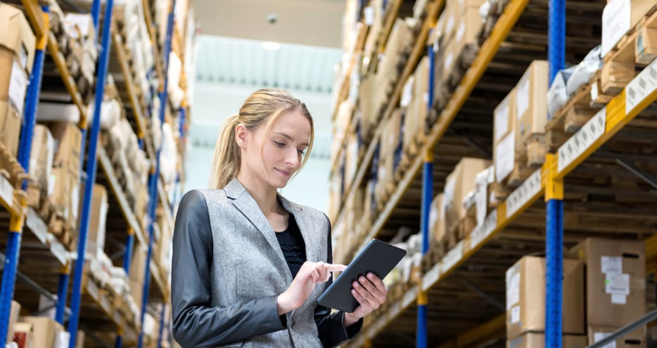 Woman looks at inventory management software on tablet