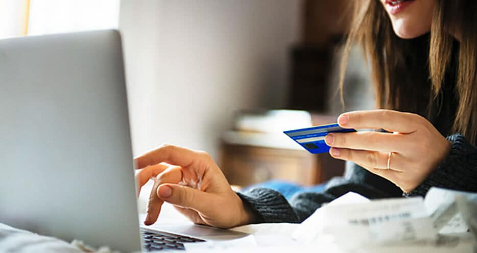 close up photo of woman holding a credit card while typing on a laptop