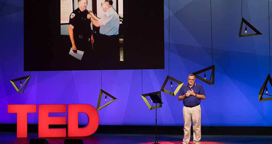 John McKown speaking on the TED stage.