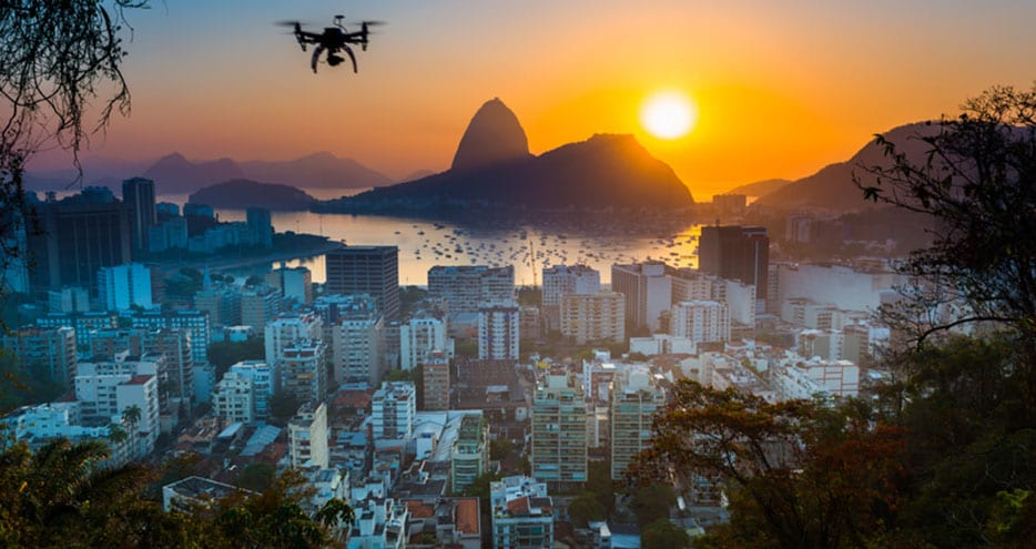 A drone hovers above Rio de Janiero at sunset.