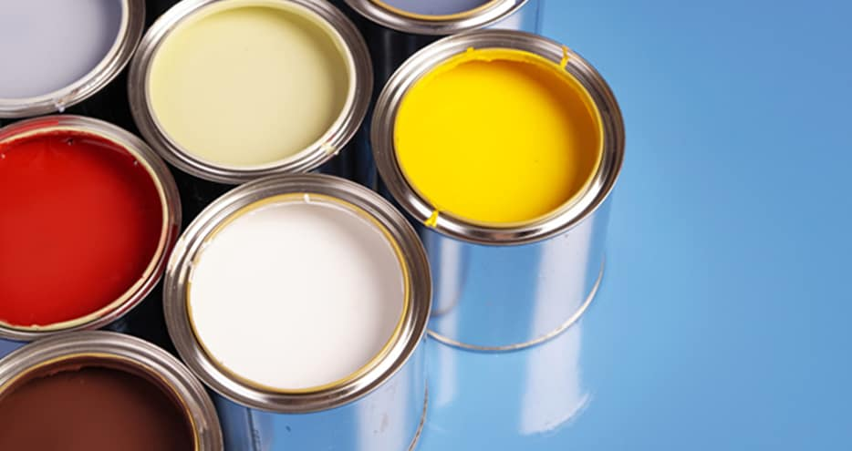 A number of open tins of paint of various colors sit on a tabletop.