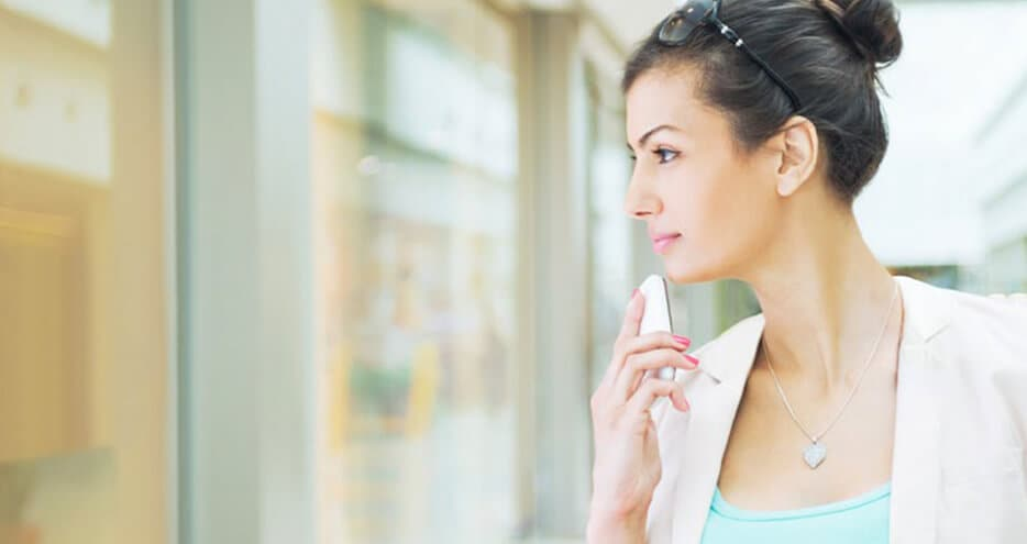Photo of a stylish woman holding a mobile phone while gazing into a storefront window.