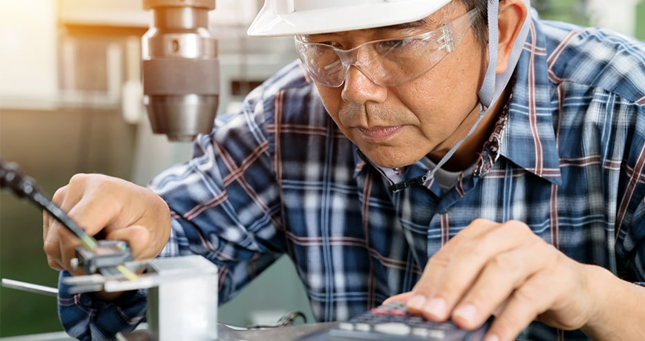 Male engineer calculating parts of production machine in factory.