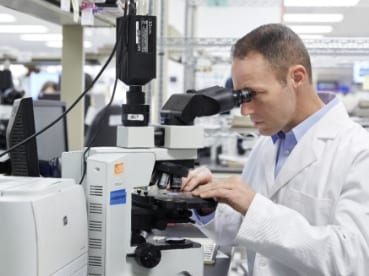 Pathologist analyzing slides using a microscope