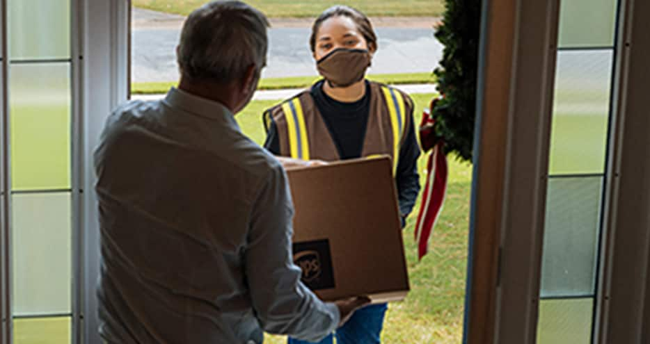 A customer opens the door of his home to hand his package to a UPS driver during a package pickup.