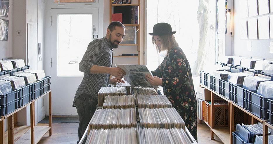 Two shoppers browsing through bins of vinyl records in a music shop.