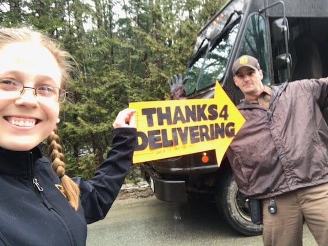 image of girl holding an arrow shaped sign towards a ups driver that says 'Thanks 4 delivering