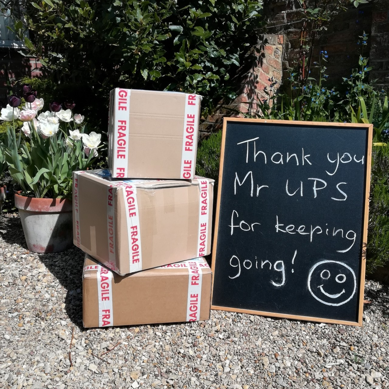 image of boxes and a chalkboard that says 'Thank you Mr. UPS for keeping going'