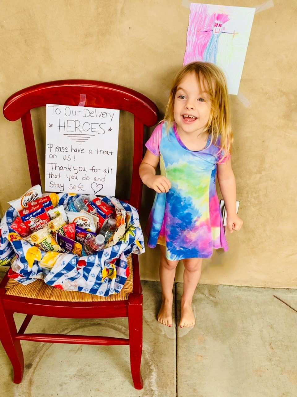 image of small child standing next to a chair with a basket of snacks and drinks and a note that says 'To our Delivery heroes. Please have a treat on us! Thank you for all that you do and Stay Safe'