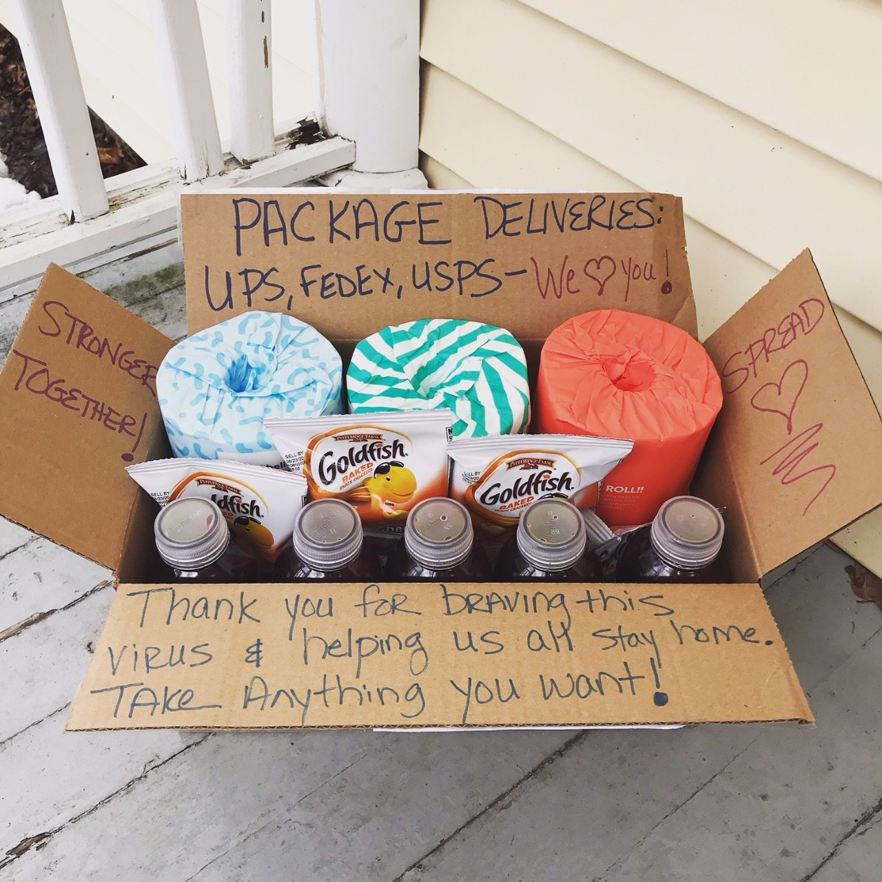 Image of a box of water, snacks and toilet paper with thank you note that says 'thank you for braving this virus and helping us all stay home'
