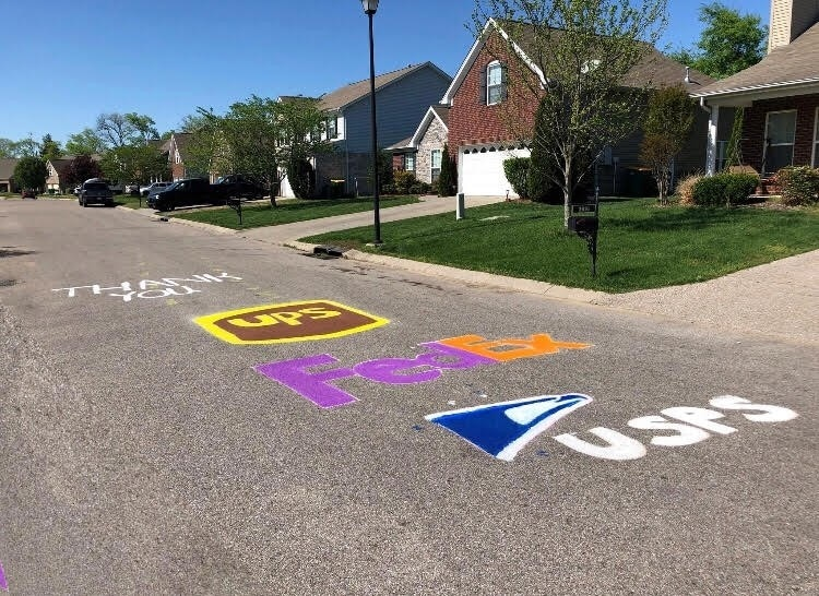 chalk art on street that says 'thank you' with the logos of UPS, FedEx, and USPS