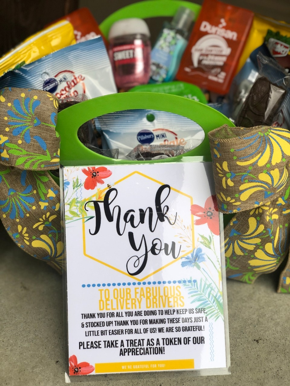 close up of basket of snacks and sanitizer with note that says 'Thank you'