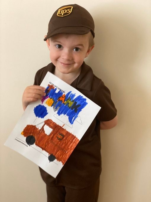 small child dressed as a UPS driver holding a coloring page that has a UPS truck on it