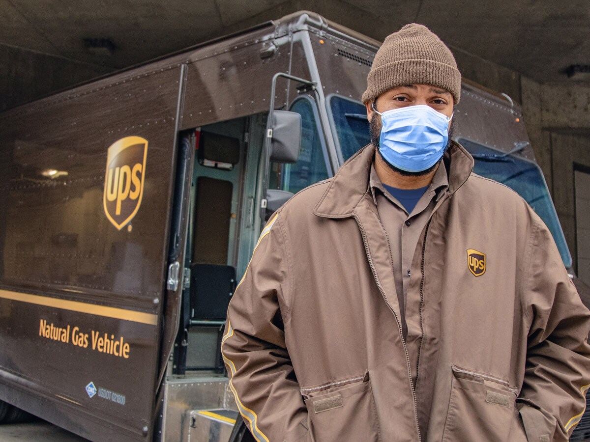 UPS driver in a mask standing in front of his truck