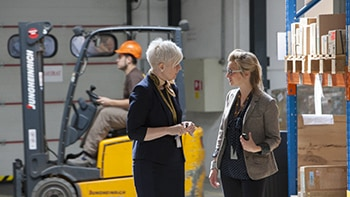 Two women discussing specialized shipping services in warehouse