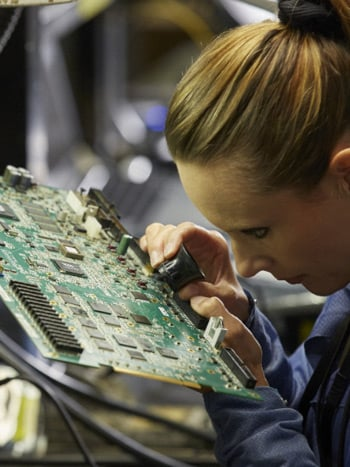 Technician inspecting motherboard at electronics factory