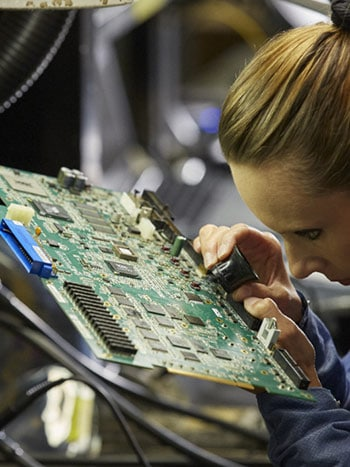 Technician inspects motherboard in warehouse