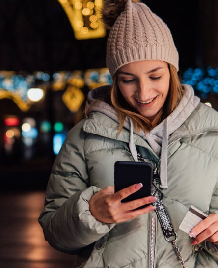 Woman on festive street shopping on phone with credit card