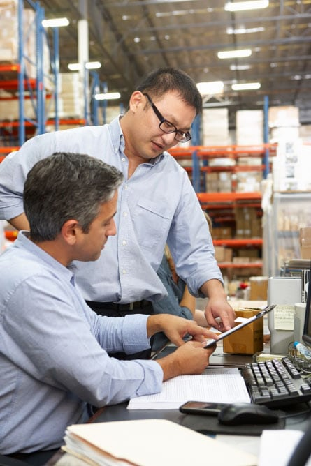 Men in warehouse using tablet
