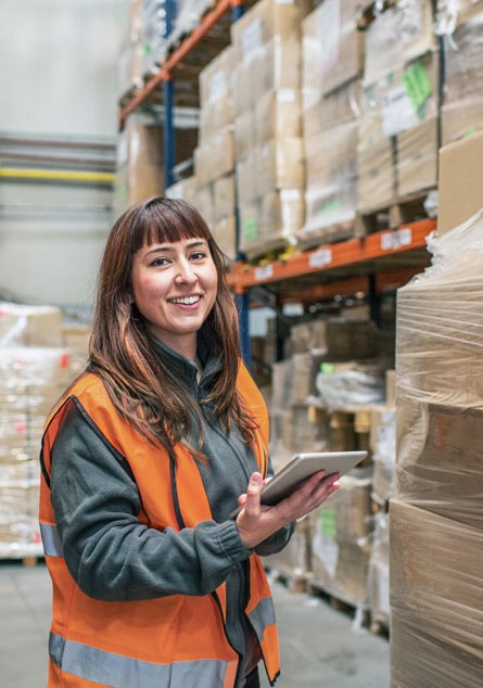 Woman in warehouse using tablet