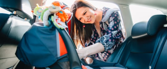 Woman preparing to load child in car seat