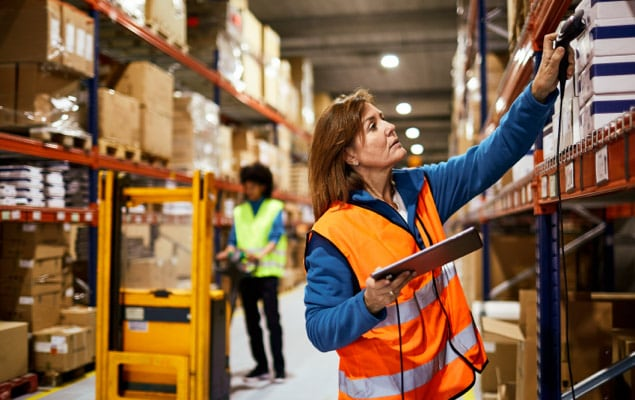 Woman in warehouse using laptop for inventory management