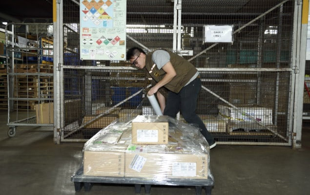 UPS employee shrink-wrapping partial-pallet shipment to hold for pick-up