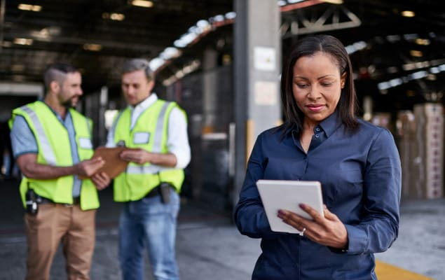 Woman in warehouse checking the status of inbound shipments