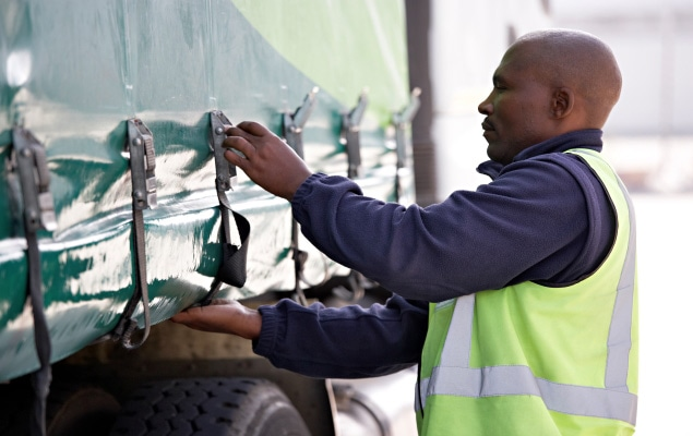 Worker securing freight shipment on trailer