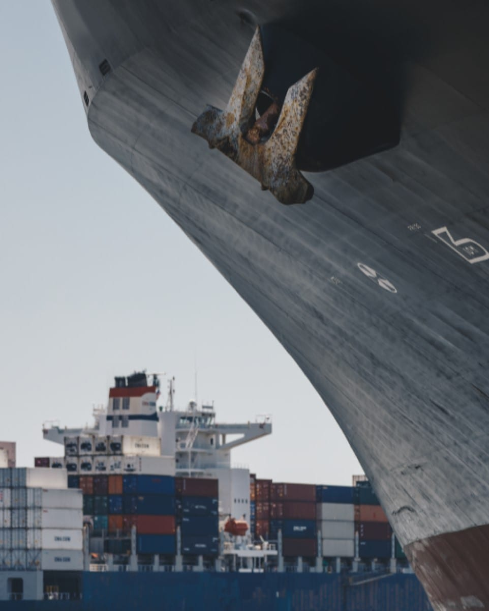 Close up of side of ship with freight ship in background