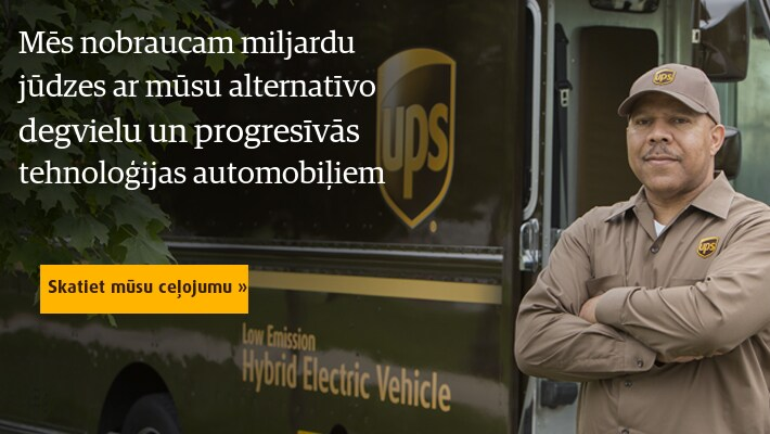 Proud UPS driver standing next to alternative fuel vehicle